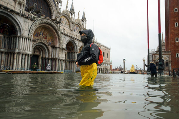 Ľudia sa brodia Námestím sv. Marka v Benátkach, ktoré sa v dôsledku silného prílivu ocitlo pod vodou.