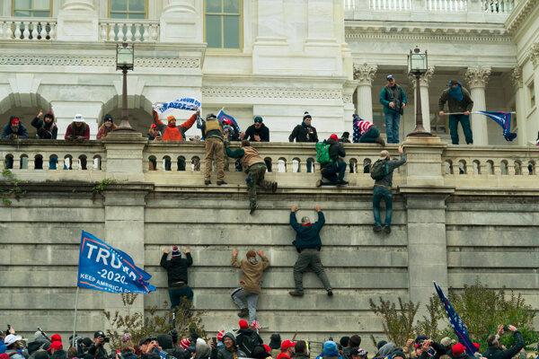 Stúpenci dosluhujúceho amerického prezidenta Donalda Trumpa sa vešajú na budovu Kapitolu vo Washingtone.