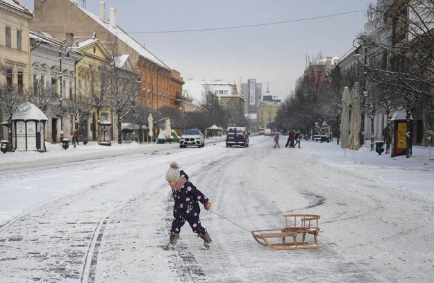 Dieťa prechádza so sánkami po zasneženej Hlavnej ulici v Košiciach.