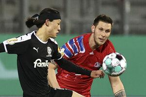 Momentka zo zápasu Kiel - Bayern Mníchov. Vpravo hosťujúci Niklas Sule, vpravo jeden z dvoch legionárov domácich, Kórejčan Lee Jae-Sun.