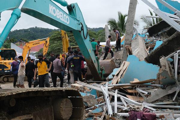 Záchranári prehľadávajú trosky budovy v indonézskom meste Mamuju.