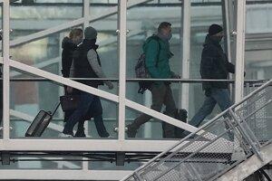 Ruský opozičný líder Alexej Navaľnyj (druhý sprava) a jeho manželka Julija (štvrtá sprava) kráčajú halou do lietadla Boeing 737-800 ruskej leteckej spoločnosti Pobeda.