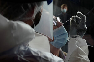 Zdravotnícky pracovník v ochrannom odeve odoberá žene vzorky z nosa počas testovania na ochorenie COVID-19 vo Francúzsku.