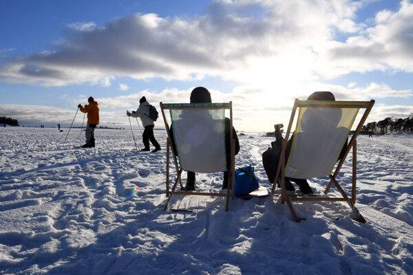 Ľudia sedia na slnku, ostatní sa lyžujú počas slnečného počasia v Helsinkách 14. februára 2021.