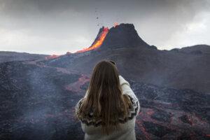 Žena si fotí vytekajúcu lávu počas erupcie sopky na polostrove Reykjanes  na juhozápade Islandu.