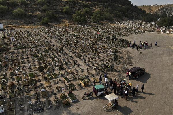 Rodinní príslušníci počas pohrebného obradu blízkej osoby, ktorá podľahla ochoreniu COVID-19, na cintoríne Chalco na predmestí mexickej metropoly v stredu 17. marca 2021.