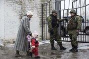 Žena sprevádza svoje dieťa počas evakuácie z mesta Avdijivka v oblasti Donbasu.