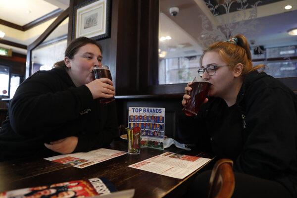 Zdravotné sestry Libby Jonesová (vpravo) a Shannon Maidenová, ktoré skončili svoju nočnú službu, pijú cider v pube Shakespeare's Head v Londýne, v ktorom po prvý raz od posledného lockdownu privítali zákazníkov vo vnútorných priestoroch.