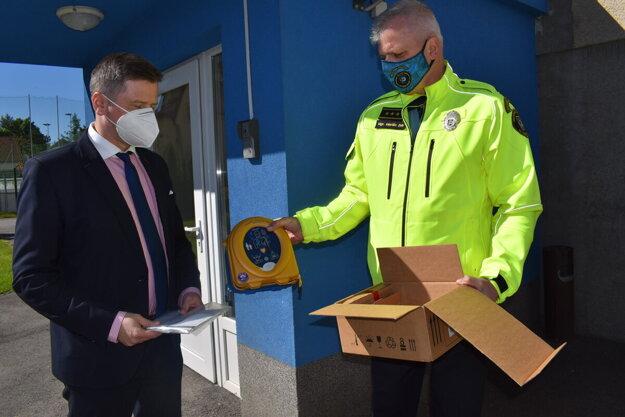 Nový defibrilátor prevzal od primátora Miloša Merička (vľavo) náčelník mestskej polície Marián Zub.