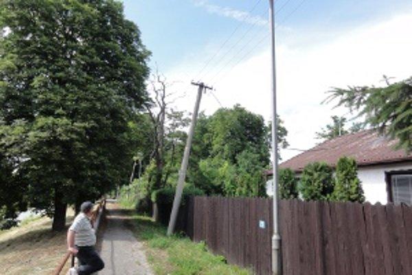 Elektrický stĺp je neprirodzene sklonený ponad rodinný dom.