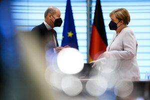 Nemecký minister Olaf Scholz hovorí s kancelárkou Angelou Merkelovou.
