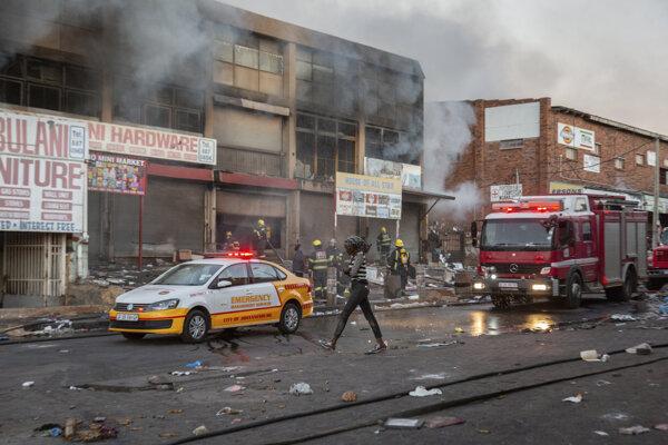 Žena kráča okolo hasičského auta v juhoafrickom Johannesburgu.