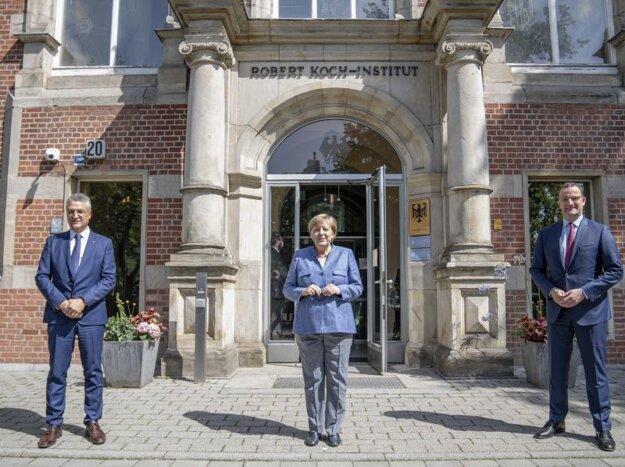 Zľava Lothar Wieler, riaditeľ Inštitút Roberta Kocha, kancelárka Angela Merkelová a minister zdravotníctva Jens Spahn počas príhovoru pred budovou inštitútu v Berlíne.