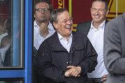 Laschet sa smial s ďalšími ľuďmi v pozadí vo chvíli keď Steinmeier poskytoval vyhlásenie pre novinárov.