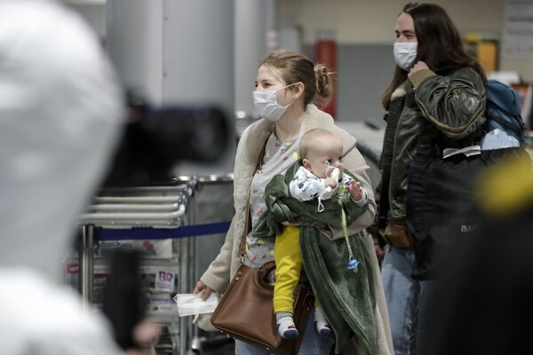 Pasažieri s ochrannými rúškami na tvárach s dieťaťom kráčajú k ruským zdravotníckym expertom počas kontroly pasažierov prichádzajúcich zo zahraničných krajín na letisku Šeremetjevo.