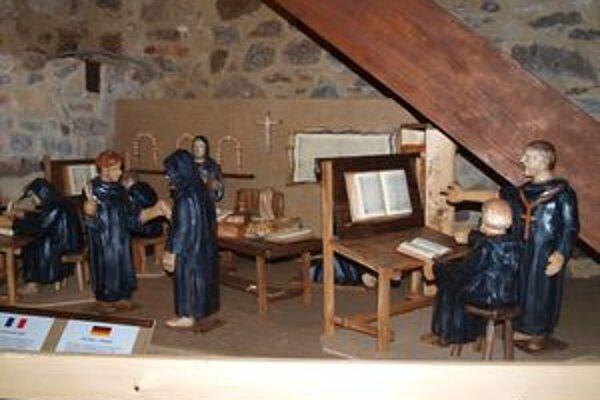 Interiér pisárne v kláštore a mníchov pri práci zobrazuje nová plastika Štefana Réckeho.