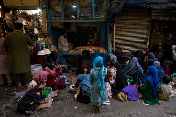 Afganské ženy a deti sedia pred pekárňou a čakajú na rozdávanie chleba.