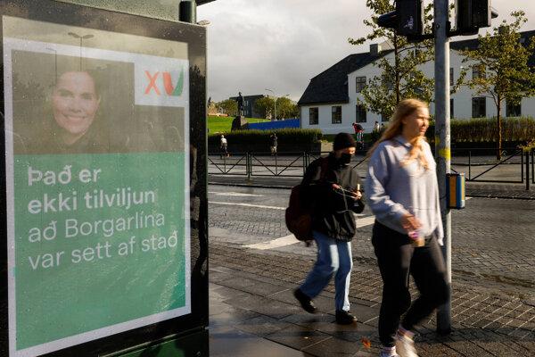 Obyvatelia Reykjavíku kráčajú okolo volebného plagátu súčasnej premiérky Katrín Jakobsdóttir.