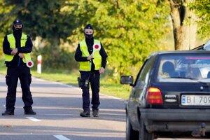 Poľská polícia pri hraničnom priechode zastavuje prichádzajúce auto.
