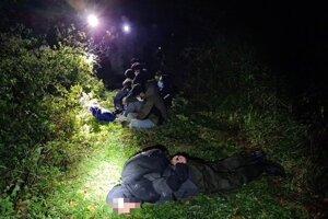 V popredí leží prevádzač, vzadu sedia migranti.