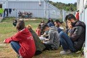 Migranti sedia pred kontajnermi v zariadení pre prvotný príjem žiadateľov o azyl v nemeckom Eisenhüttenstadte