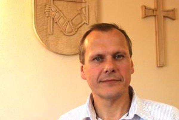 Ondrej Ščurka pred mestským erbom, ktorý má vo svojej kancelárii.