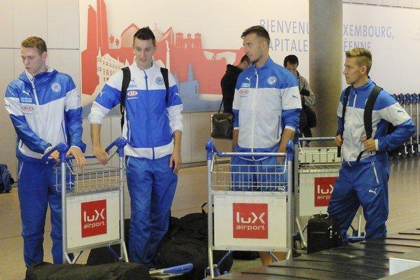Kvarteto mladíkov z futbalovej reprezentácie (zľava stoja: Duda, Greguš, Gyömbér a Hrošovský) čaká na batožinu po prílete do Luxemburgu.