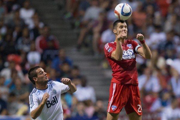 Octavio Rivero z tímu Vancouver Whitecaps sa prizerá, ako hlavičkuje loptu jeho súper Matt Hedges z Dallasu.