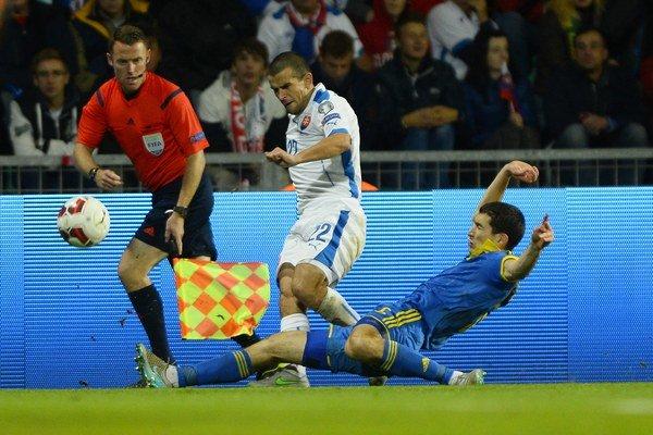 Viktor Pečovský (s číslom 22) patrí medzi dôležité postavy slovenského národného tímu v kvalifikácii o postup na majstrovstvá Európy 2016. Na snímke zo súboja proti Ukrajine odkopáva loptu pred Tarasom Stepanenkom.