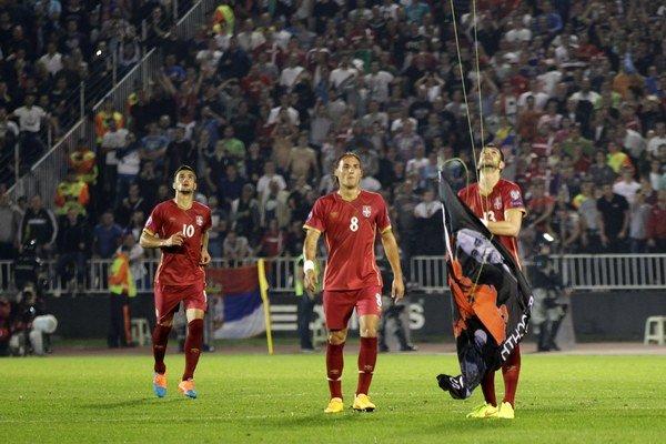 Srbský futbalista Stefan Mitrovič reaguje na provokáciu a strháva albánsku vlajku, ktorá lietala na minihelikoptére nad štadiónom. Následne sa na ihrisku strhla bitka.