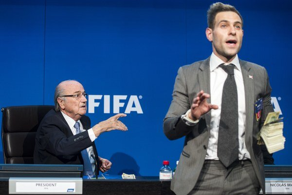 Britský komik Simon Brodkin začal hádzať na prezidenta FIFA Sepa Blattera falošné bankovky.