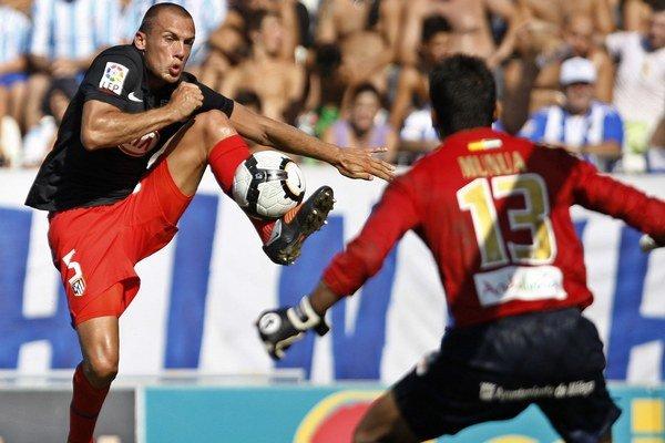 Heitinga (vľavo) ešte v drese Atlética Madrid sa pokúša skórovať.