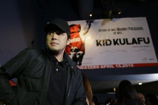 """Režisér Paul Soriano stojí pred plagátom propagujúcim jeho film """"Dieťa Kulafu"""" o boxerovi Mannym Pacquiaovi."""