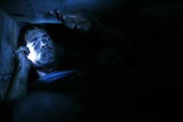Pochovaný. Baterku aj mobilný telefón Paul Conroy (Ryan Reynolds) má. Ako sa dostane spod zeme von?
