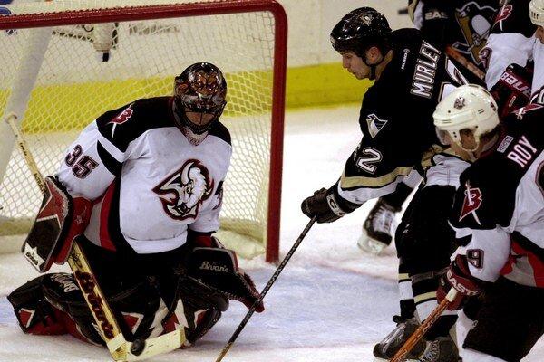 Brankár tímu Buffalo Sabres Fín Mika Noronen zasahuje proti strele Matta Murleyho (druhý zľava) z mužstva Pittsburgh Penguins počas zápasu NHL 16. decembra 2003.