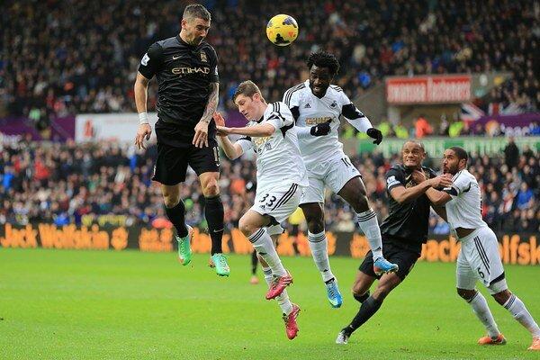 Útočník Swansea Wilfried Bony (uprostred) hlavičkuje na bránku Manchesteru City.