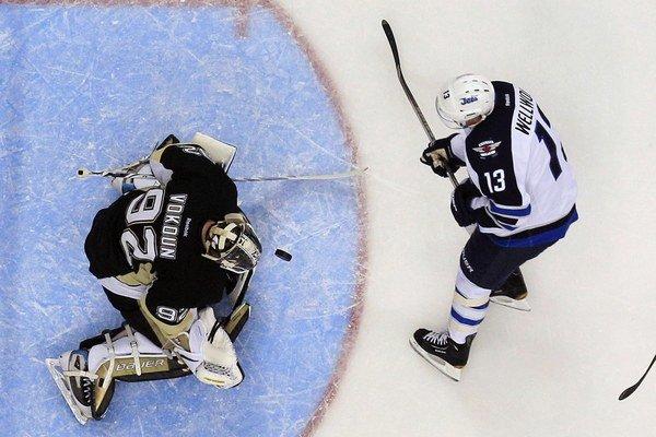 Český brankár Penguins Tomáš Vokoun úspešne zasahuje, strieľa center Jets Kyle Wellwood. Pittsburgh zdolal Winnipeg 4:0.