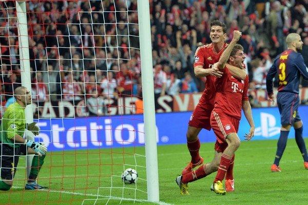 Hráč Bayernu Mníchov Thomas Müller (druhý sprava) oslavuje so svojím spoluhráčom Mariom Gomezom prvý gól do bránky Barcelony.