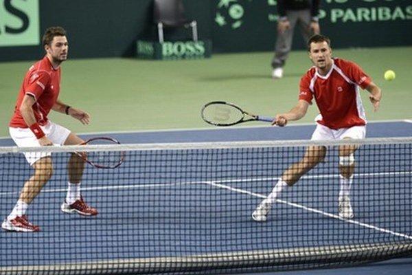 Švajčiarski tenisti Stanislas Wawrinka (vľavo) a Marco Chiudinelli počas zápasu.