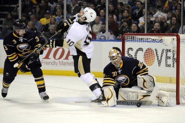 Jordan Leopold (3) z Buffalo Sabres udiera do tváre Tannera Glassa (10) z  Pittsburghu.