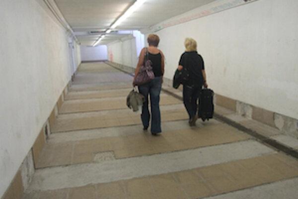 Cestujúci prechádzajú cez rozbitý podchod.