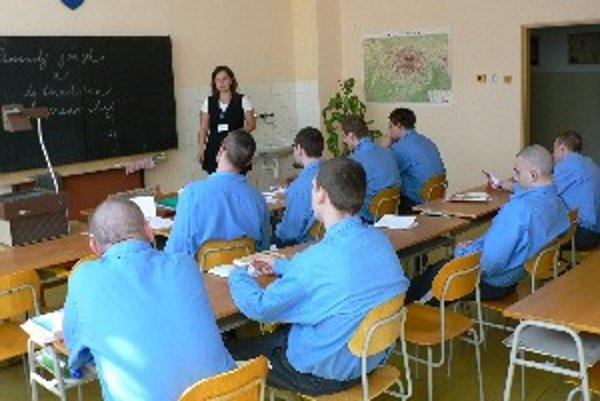 Desať odsúdených pozorne počúva učiteľku slovenkého jazyka.