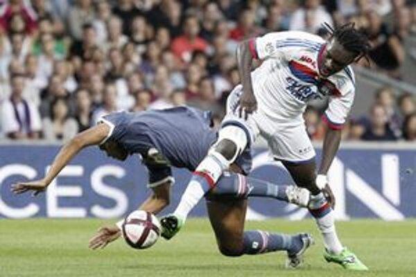 Futbalista Lyonu Bafe Gomis (vpravo) a hráč Bordeaux Carlos Henrique Dos Santos Souza bojujú o loptu počas zápasu francúzskej Ligue 1 v Lyone.