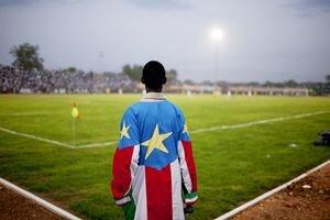 Chlapec oblečený vo farbách národnej vlajky na futbalovom štadióne v Južnom Sudáne.