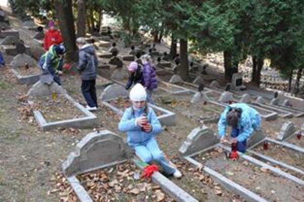 Deti zo základných škôl kladú na vojenské hroby papierové vlčie maky a zapaľujú sviečky.