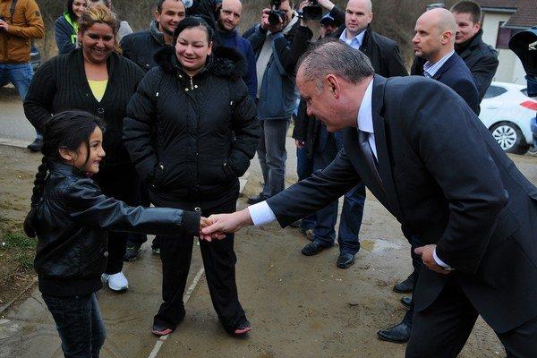 Prezident Andrej Kiska sa zdraví s rómskym dievčatkom počas návštevy obce Spišský Hrhov pri príležitosti Medzinárodného dňa Rómov 8. apríla 2015.