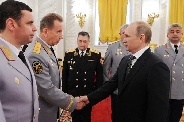 Ruský prezident Vladimír Putin si podáva ruku s veliteľom zložiek ruského ministerstva vnútra Viktorom Zolotovom pri stretnutí s vyššími dôstojníkmi v Kremli v Moskve. Putin nariadil vytvorenie nového výboru pre presadzovanie práva, národnej gardy, ktorá bude fungovať práve pod vedením Viktora Zolotova.