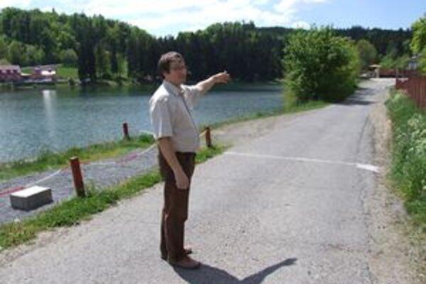 Starosta Stanislav Neuschl ukazuje pri jazere Vindšachta miesto, kde by mali vzniknúť nové parkovacie miesta.