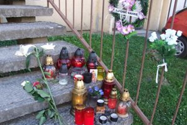 Na miesto tragédie prinášajú ľudia sviečky a kvety.