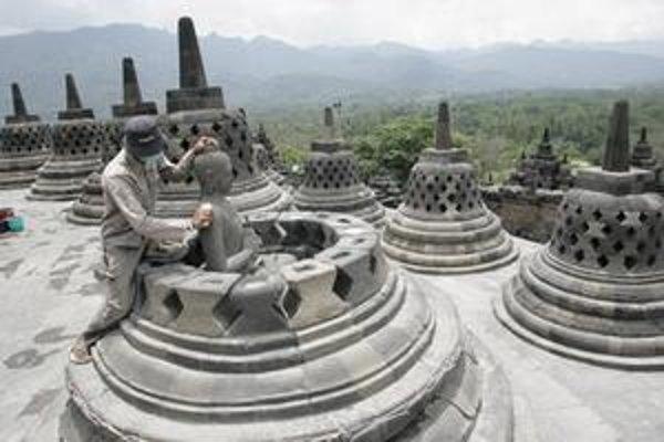 Ochranka chrámu Borobudur čistí Buddhovu sochu od popola.